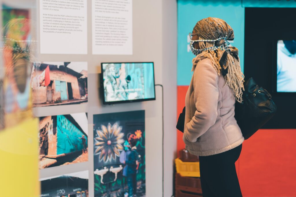 A woman is standing in BOM gallery with her hands in her pockets. She is wearing a bandana and a face covering. She is looking at some photographs on the wall.